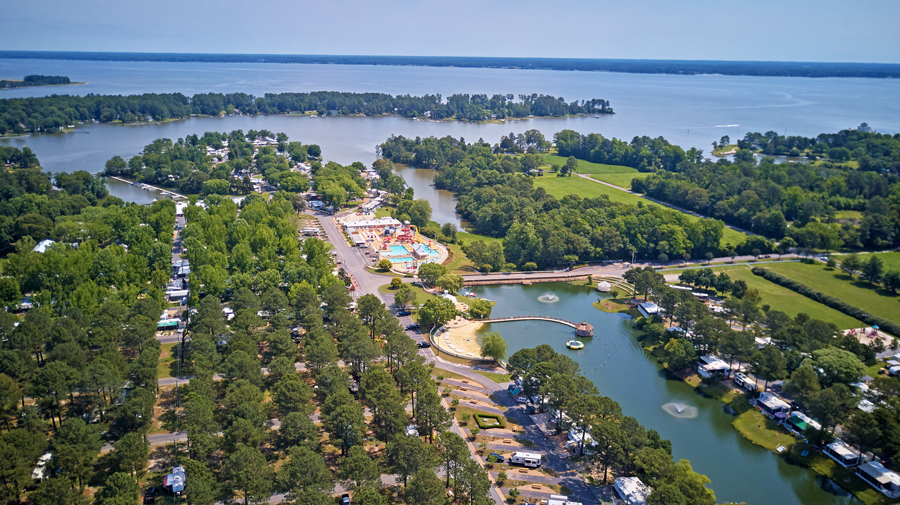 An aerial view of a riverside RV resort with a canal running through.