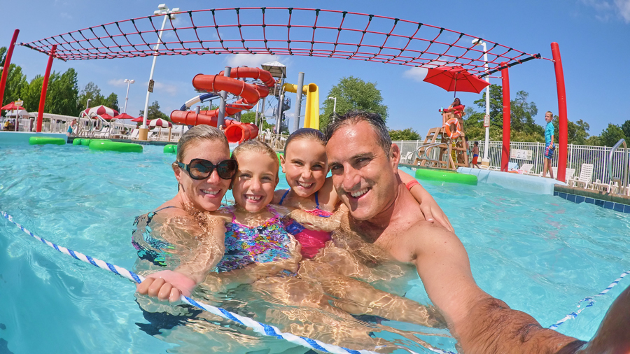 Parents and their two children pose for a selfie in a swimming pool with waterslide in the background.