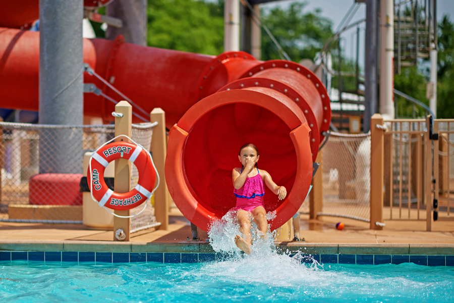 A young girl shoots out of a waterslide.