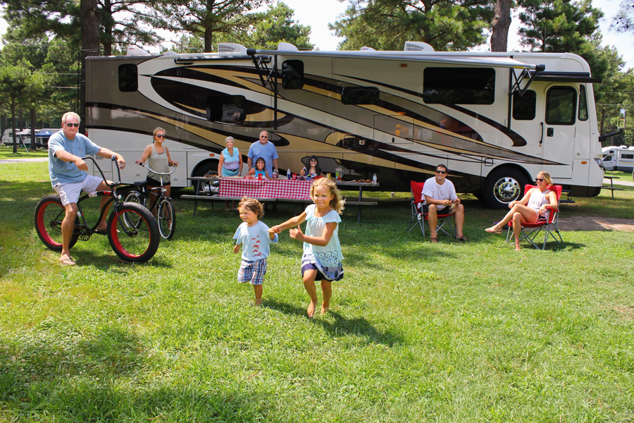 A family plays on a lawn near a motorhome.