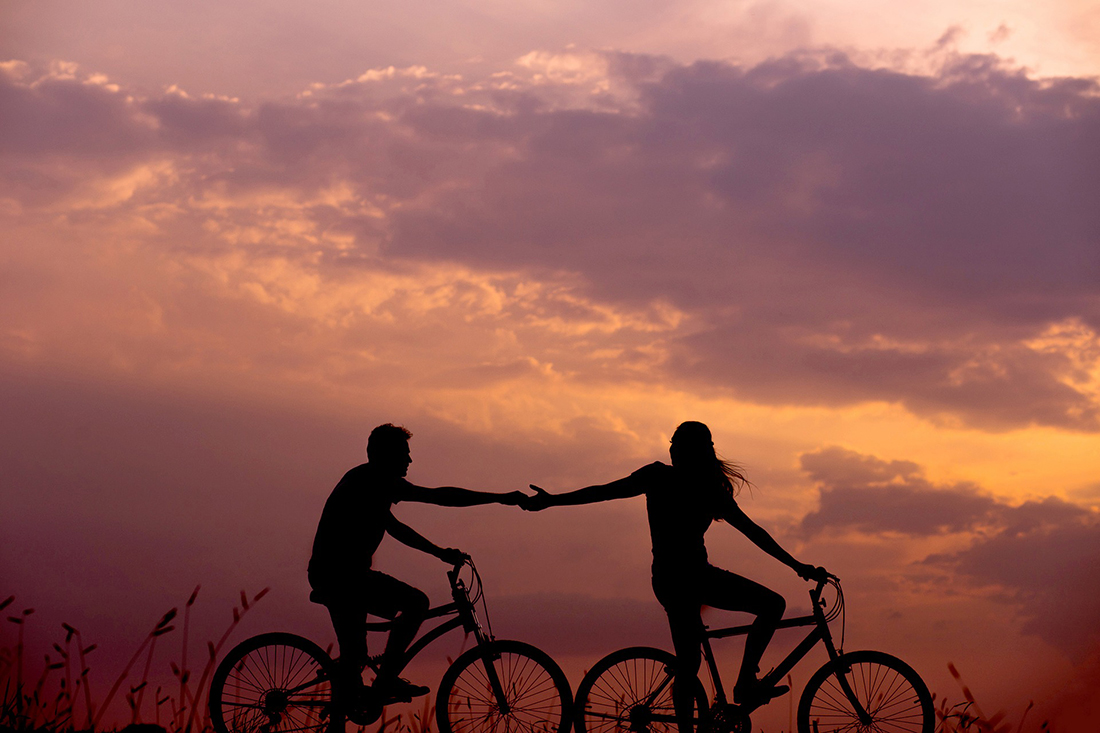 A pair of bicyclists in silhouette hold hand against a red dusk sky.
