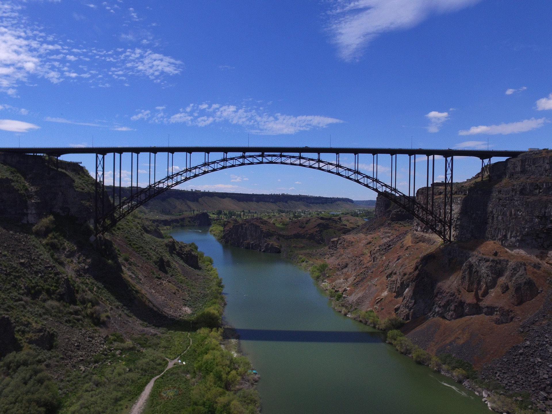 A metal bridge arching over a river gorge.