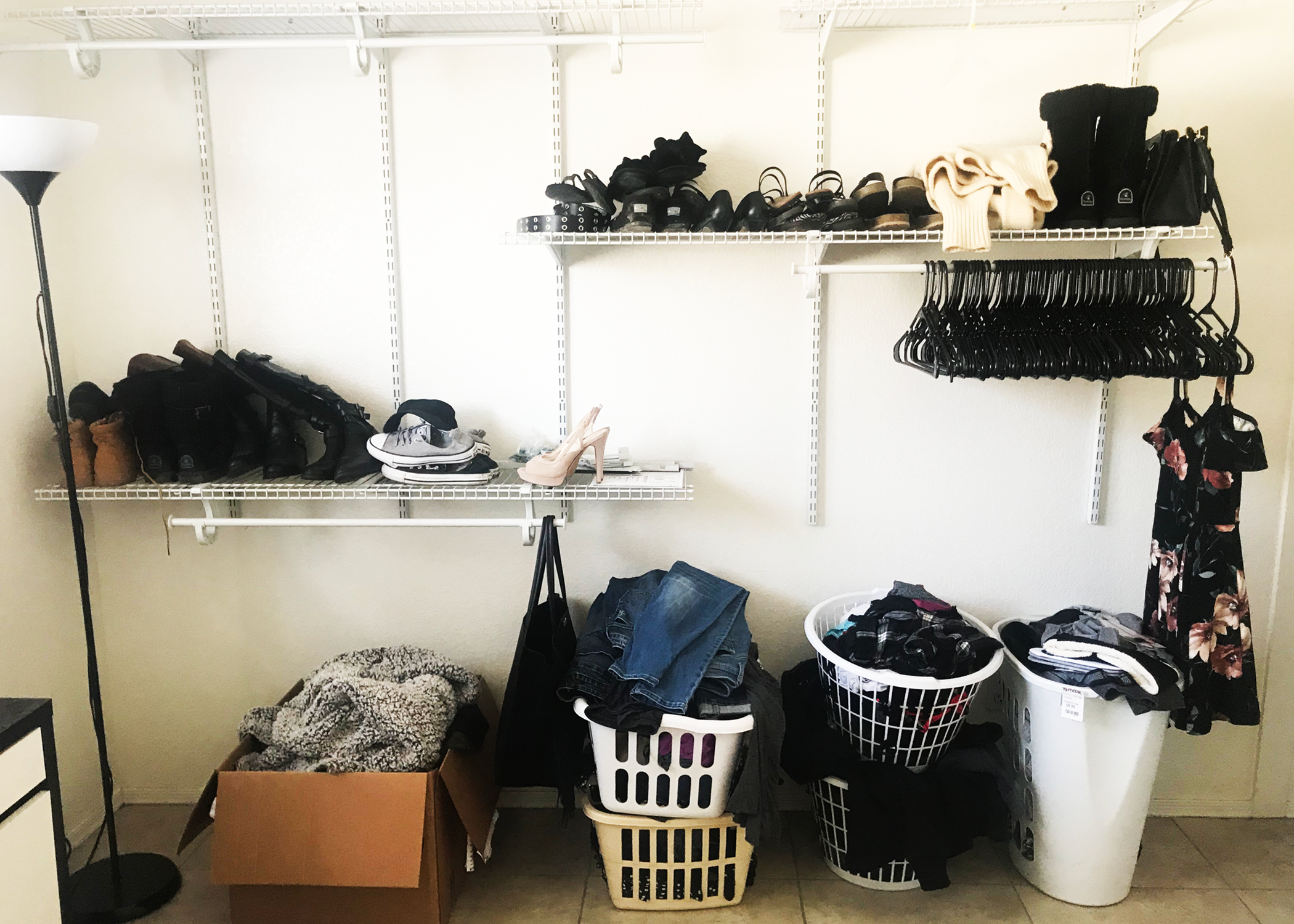 A shelving set against a wall with shoes and folded clothes.