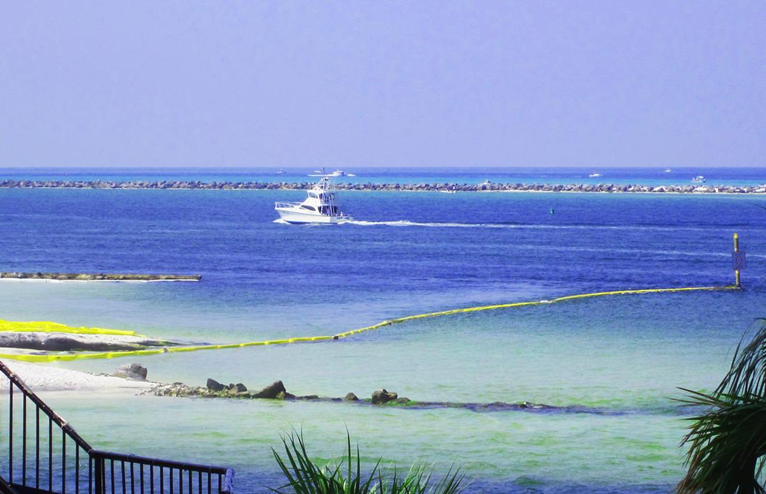 A power boat motors along a channel on blue ocean water formed by a rocky jetty.