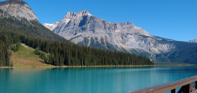 Beautiful emerald lake with pine trees and snow covered mountains