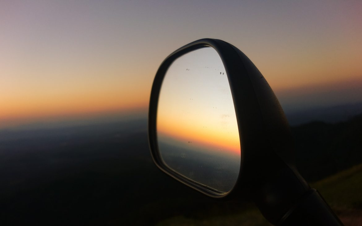 A side mirror reflects a dusk sky.