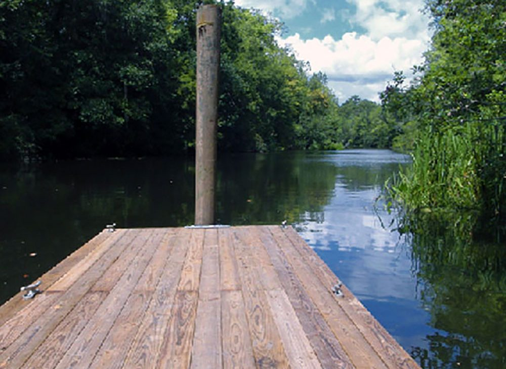 A dock just out onto a lazy rivers shadows with trees on the bank.