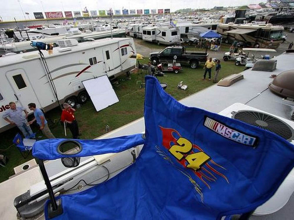 A blue folding chair on top of an RV at the Charlotte Raceway.