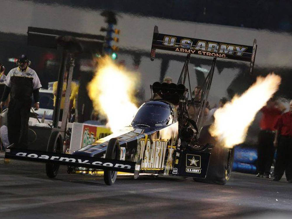 A drag racer shoots flames as it rockets off the starting line.