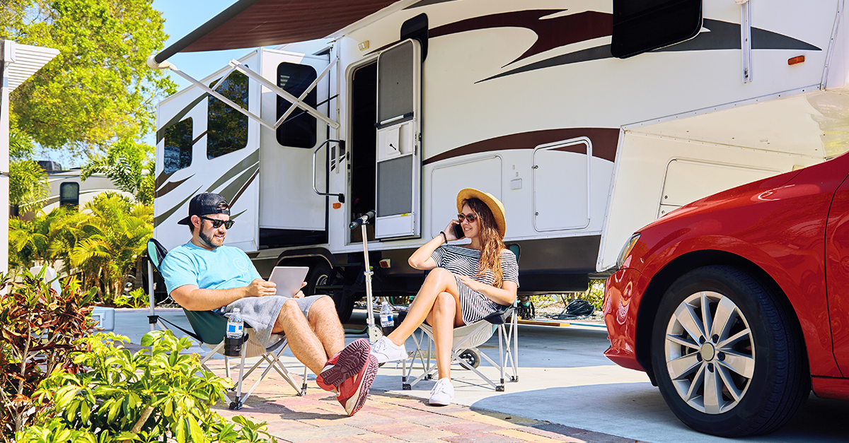 A young couple lounge outside their RV. She chats on the phone, he looks at a tablet.