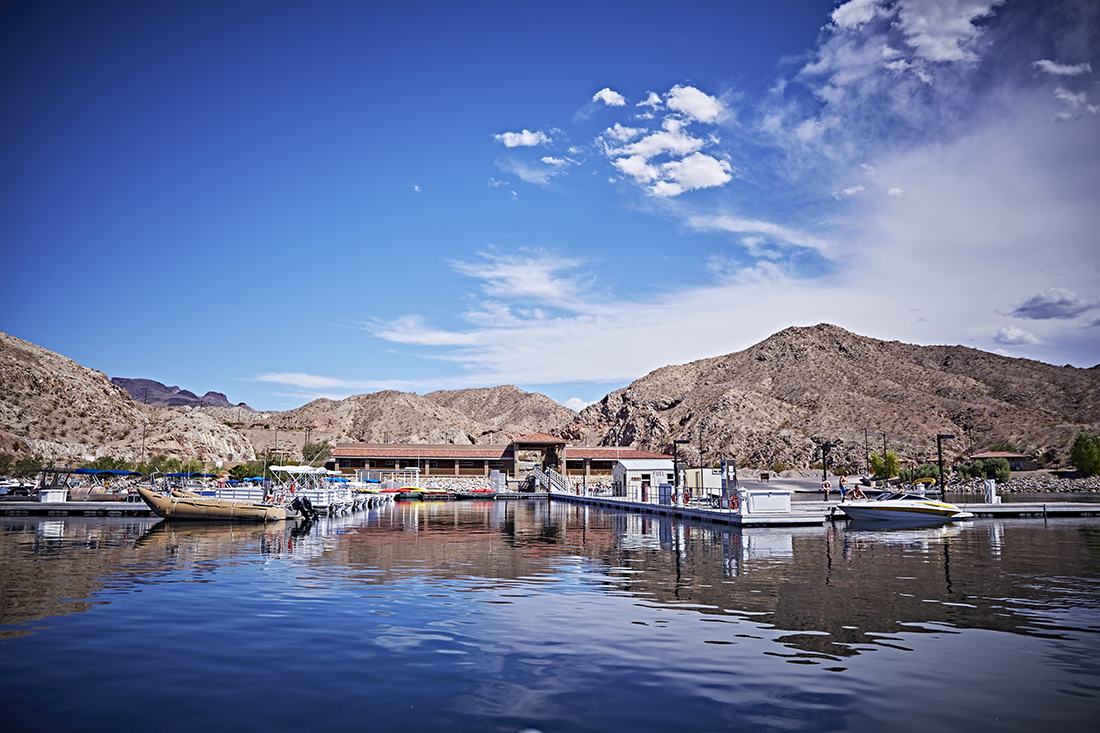 Boats docked at a marina with rugged desert hills in the background.