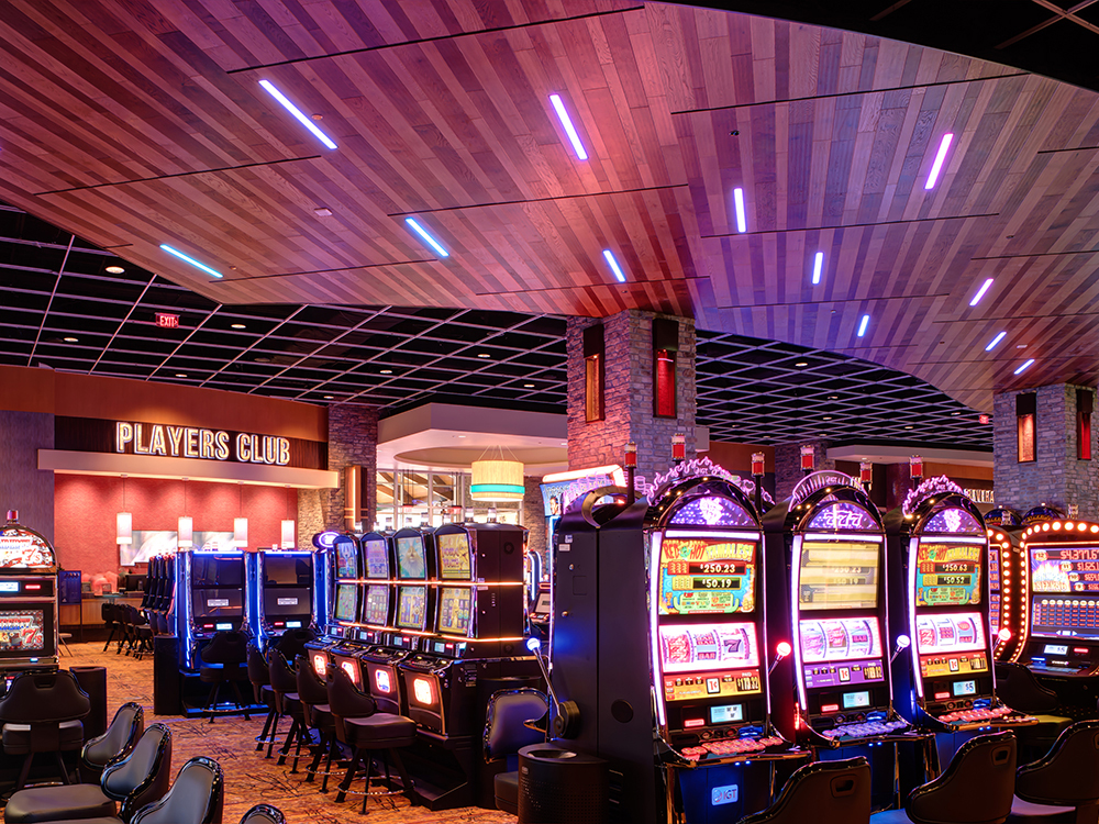 """Colorful slot machines on the casino floor with a """"players club"""" sign in the background."""