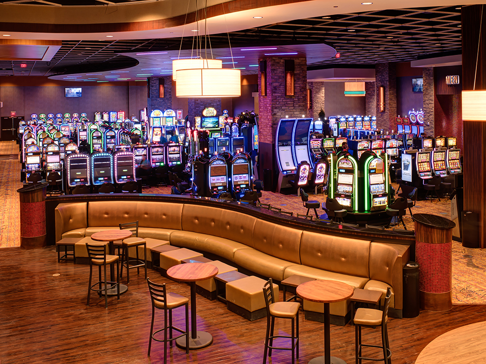 A colorful array of brightly lit slot machines with cocktail tables in the foregroundd.