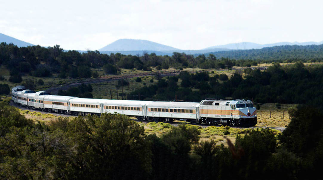 A train rolls on a track that curves through a hilly, forested landscape.