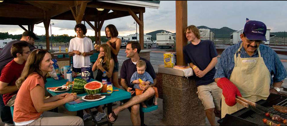 A family gathers for a cookout at picnic tables with RVs in the background.