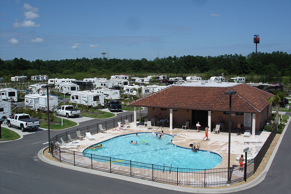 A pool in an RV park with bathers enjoying the water.