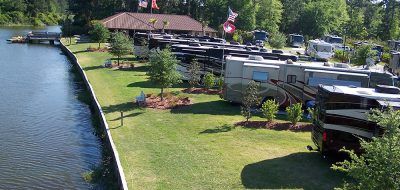 RVs parked along a strip of lawn and a tranquil waterway.