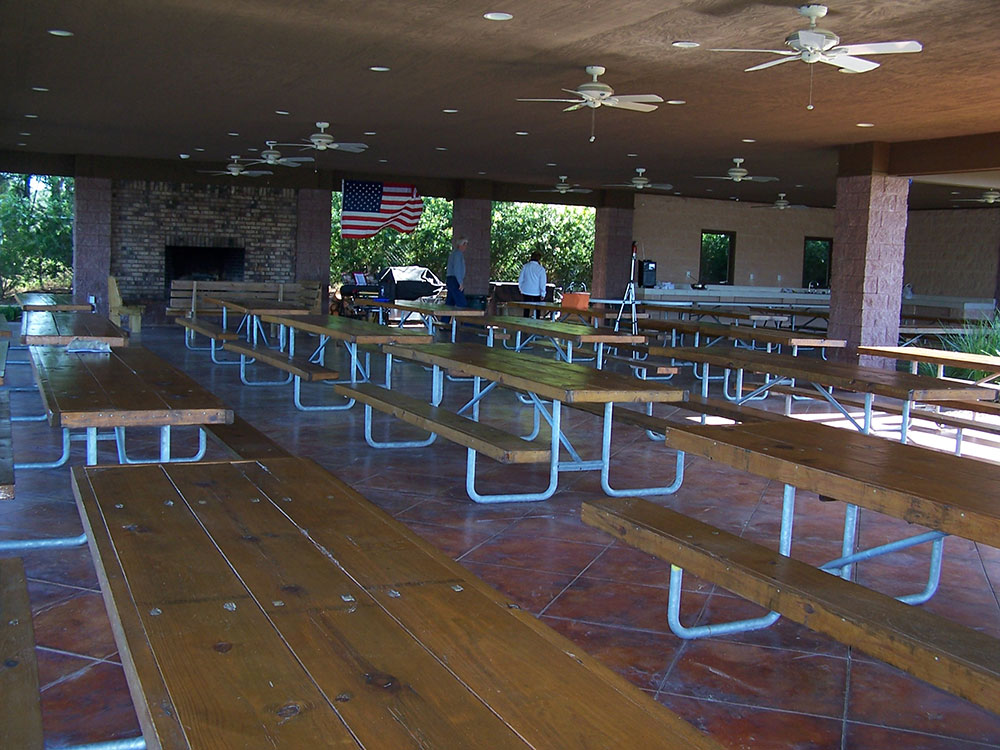 Tables fill a dining hall with a fireplace, red tile floors and ceiling fans