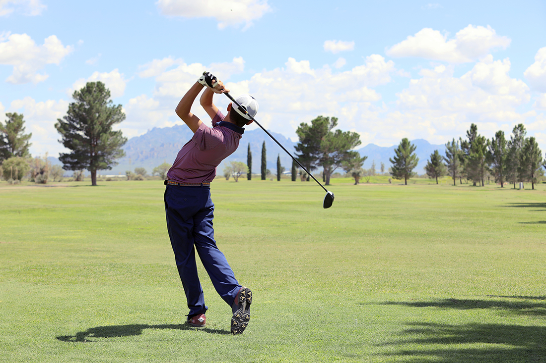Wearing a white cap, a golfer with a wood drives his ball out onto a grassy fairway with trees and hills in the distance.