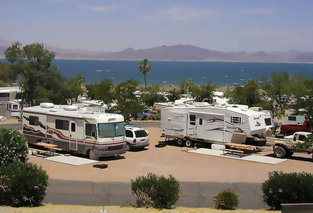 A motorhome and fifth-wheel in the foreground of a lakeside campground on Lake Mead.