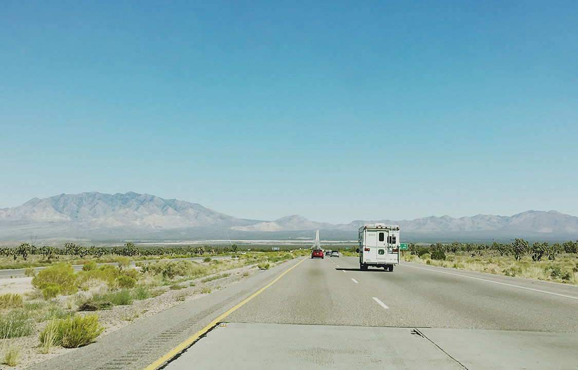 A truck camper rolls down an arid Nevada highway on a clear day.