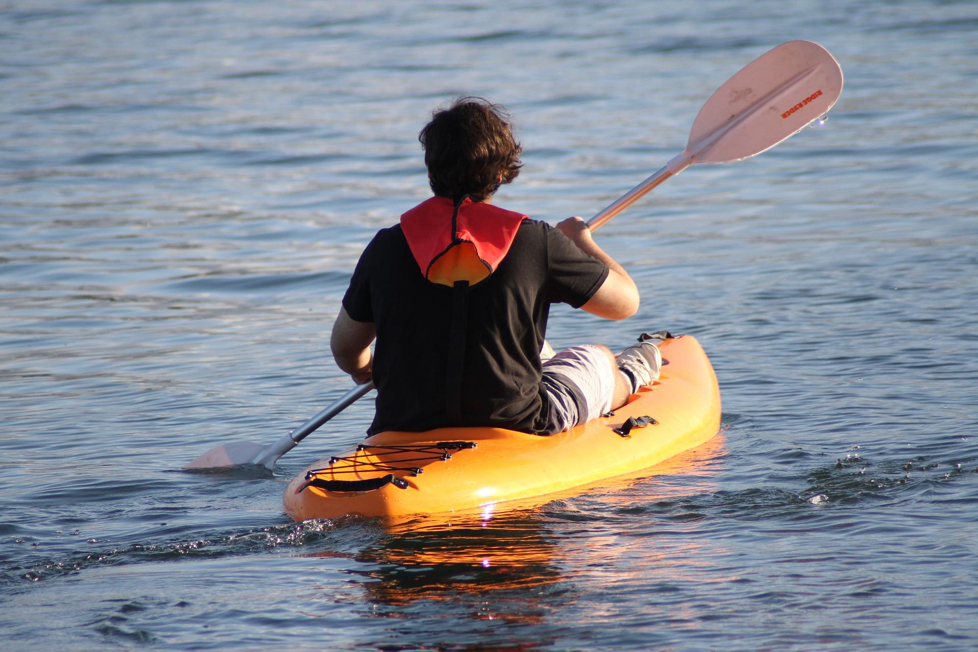 Paddling on an orange kayak.