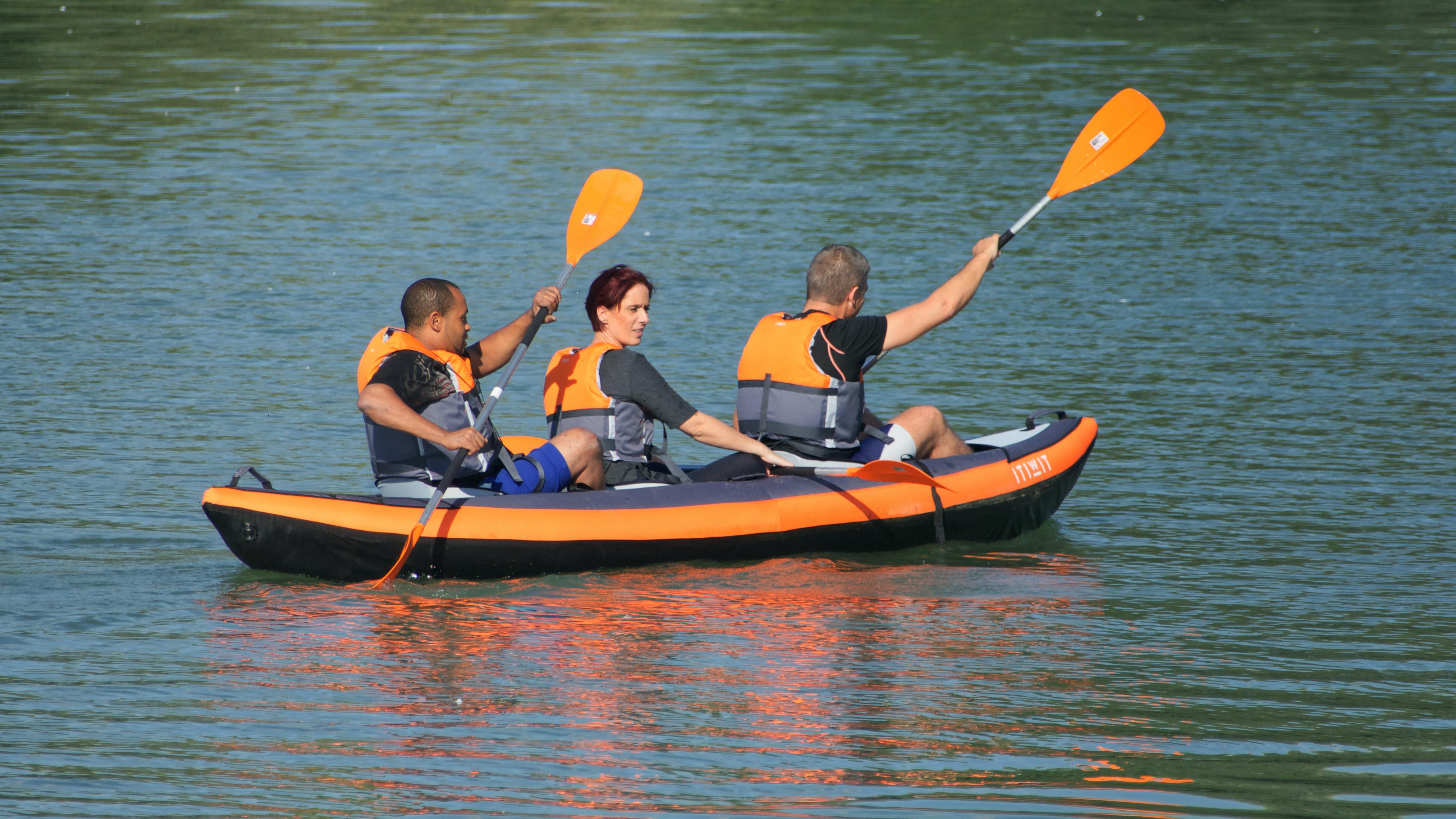 Three people paddling on a kayak.