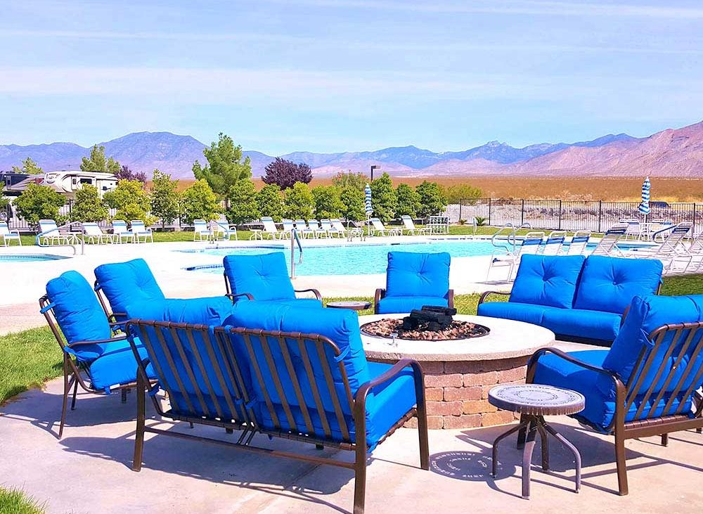 Blue patio chairs around fire pit near pool