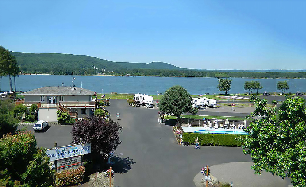 A view of an RV park overlooking a river from a high angle.