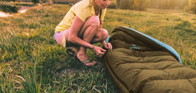Woman on grass zipping up sleeping bag