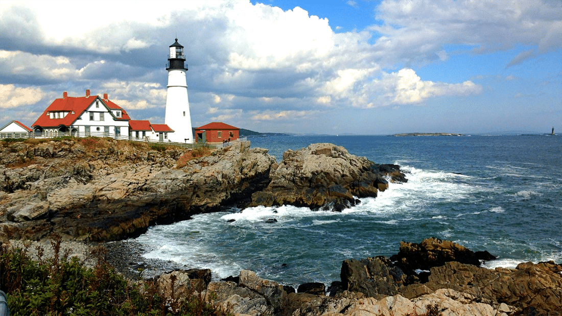 A white lighthouse sits on a rocky outcropping on the ocean in Maine.