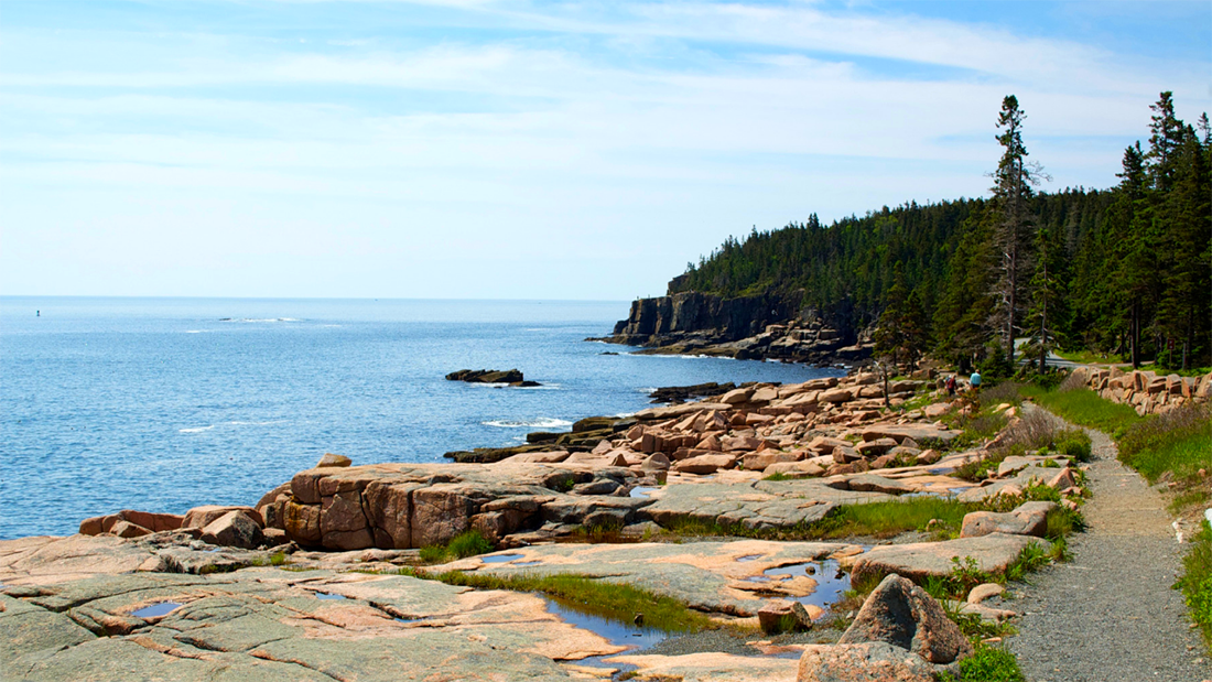 A smooth path runs parallel to the rocky shore of a beach.