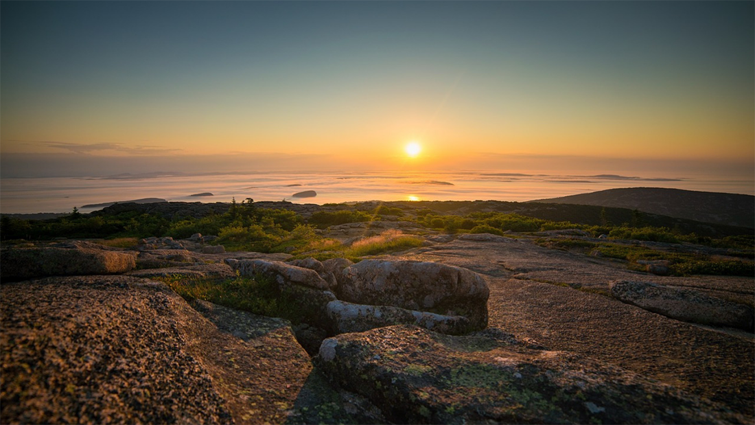 The sun rises above the ocean horizon and sheds low morning light on large smooth rocky surface of a mountain.