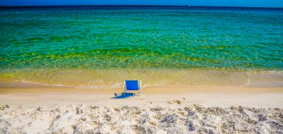 An empty blue chair on the gorgeous beach of Orange Beach, Alabama