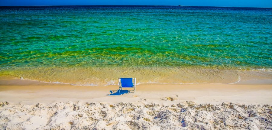 An empty blue chair on the gorgeous beach of Orange Beach, Alabama