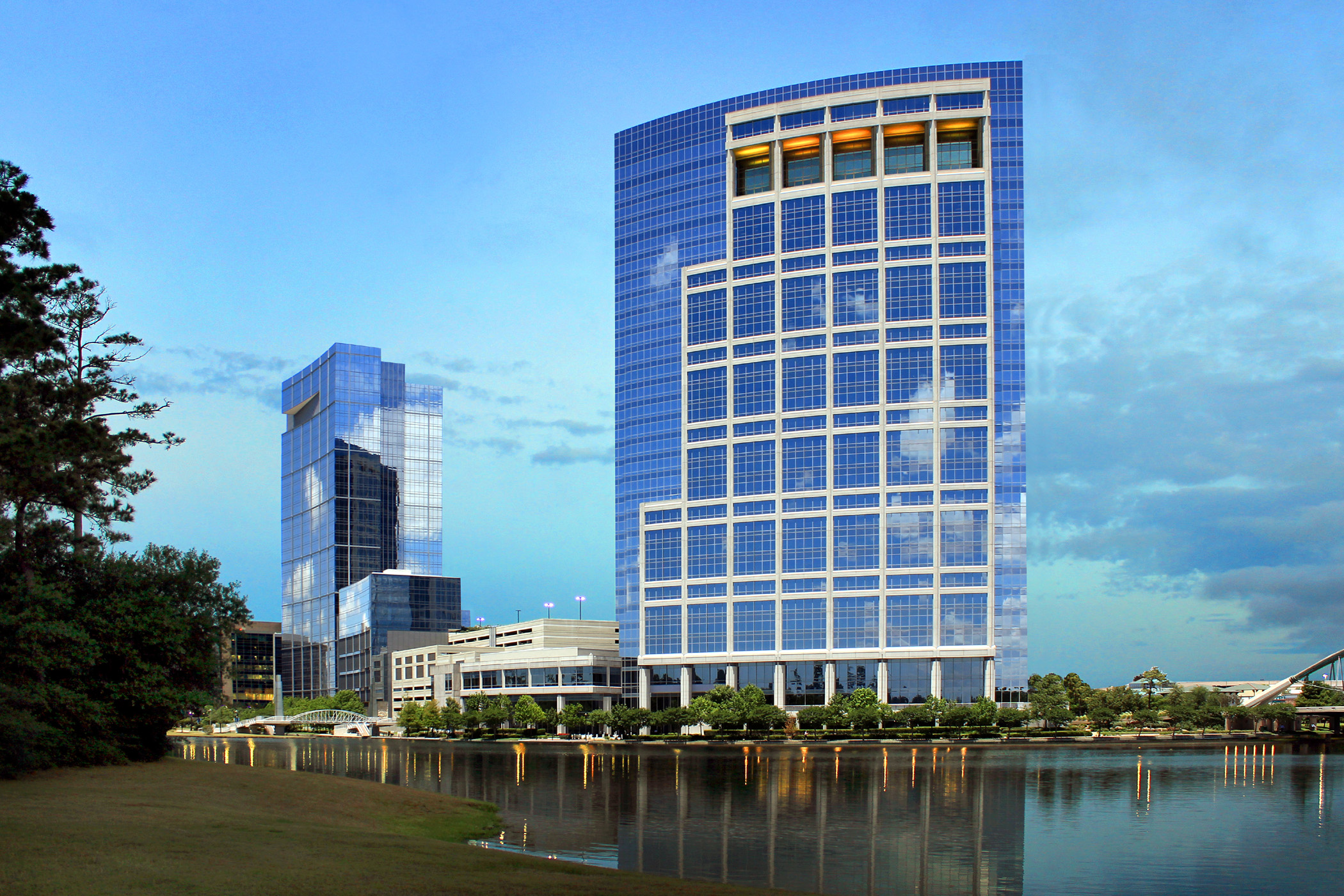 A gleaming office building reflected on the surface of a river
