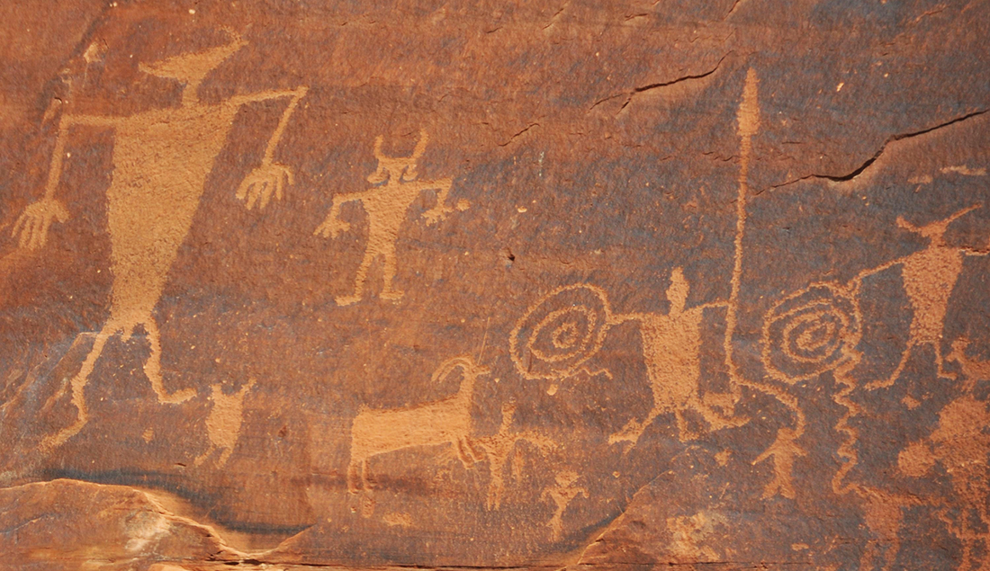 Petroglyphs figures of humans and animals carved on a rock face.