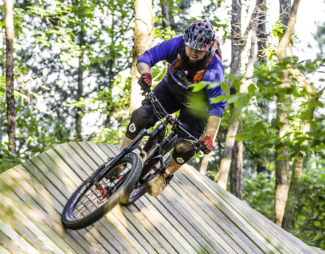 A bicycle rider takes a banked turn on a track made of wood in a forest setting.