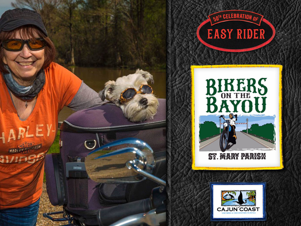 A woman in an orange Harley shirt and her dog smile.