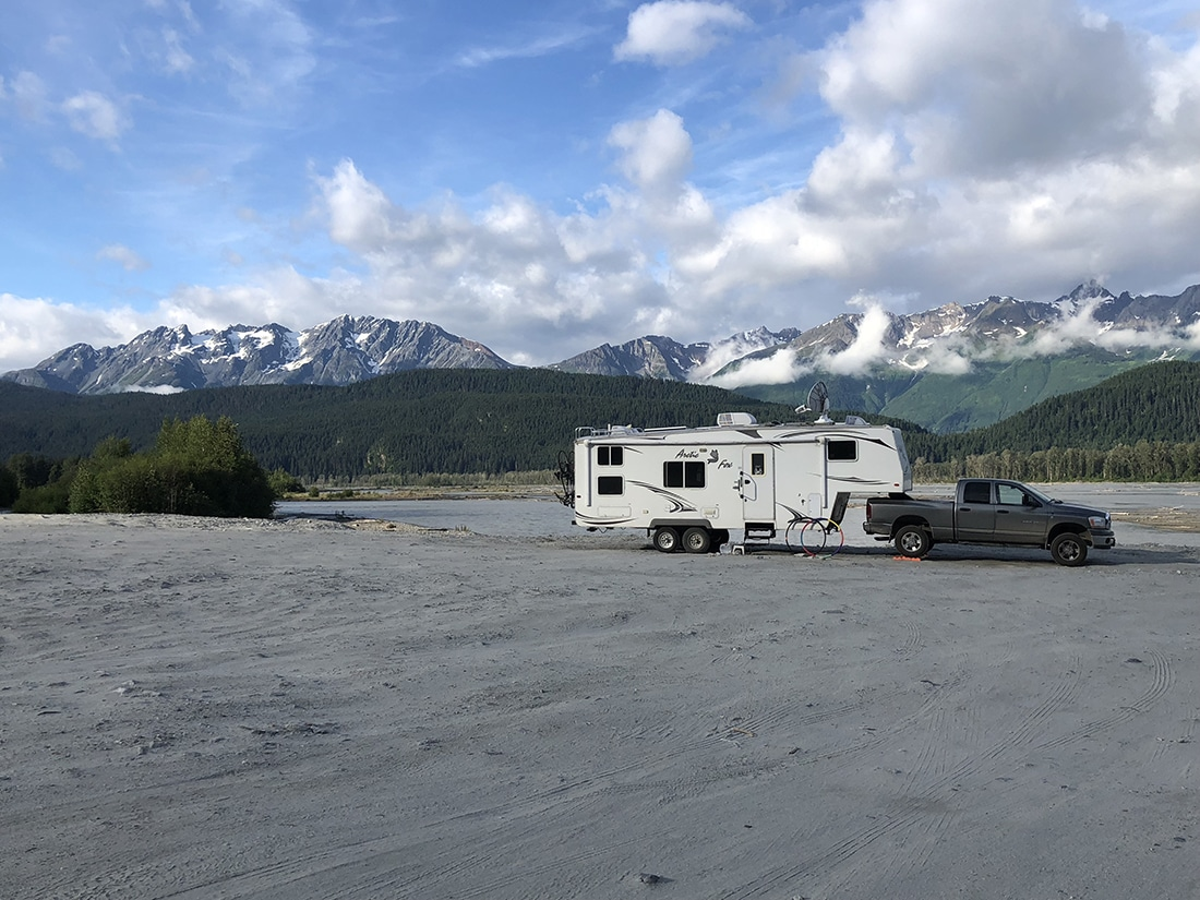A fifth-wheel trailer parked in the sand with mountains on the horizon.
