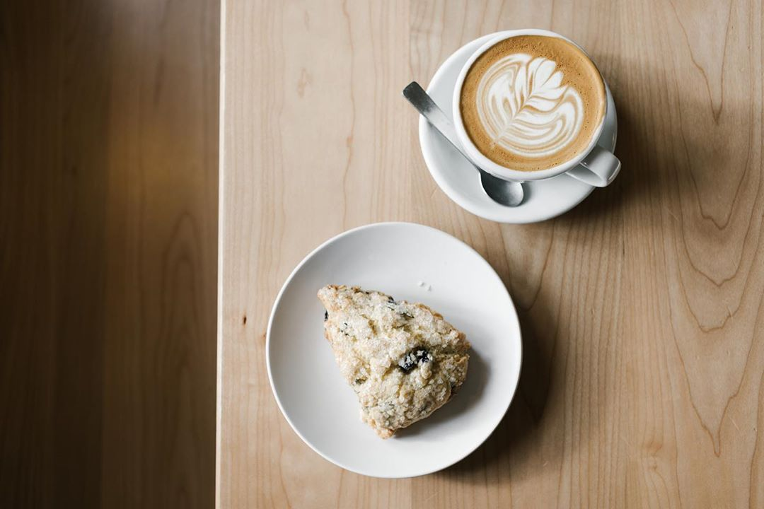 A cup of coffee with a scone on a wooden table.