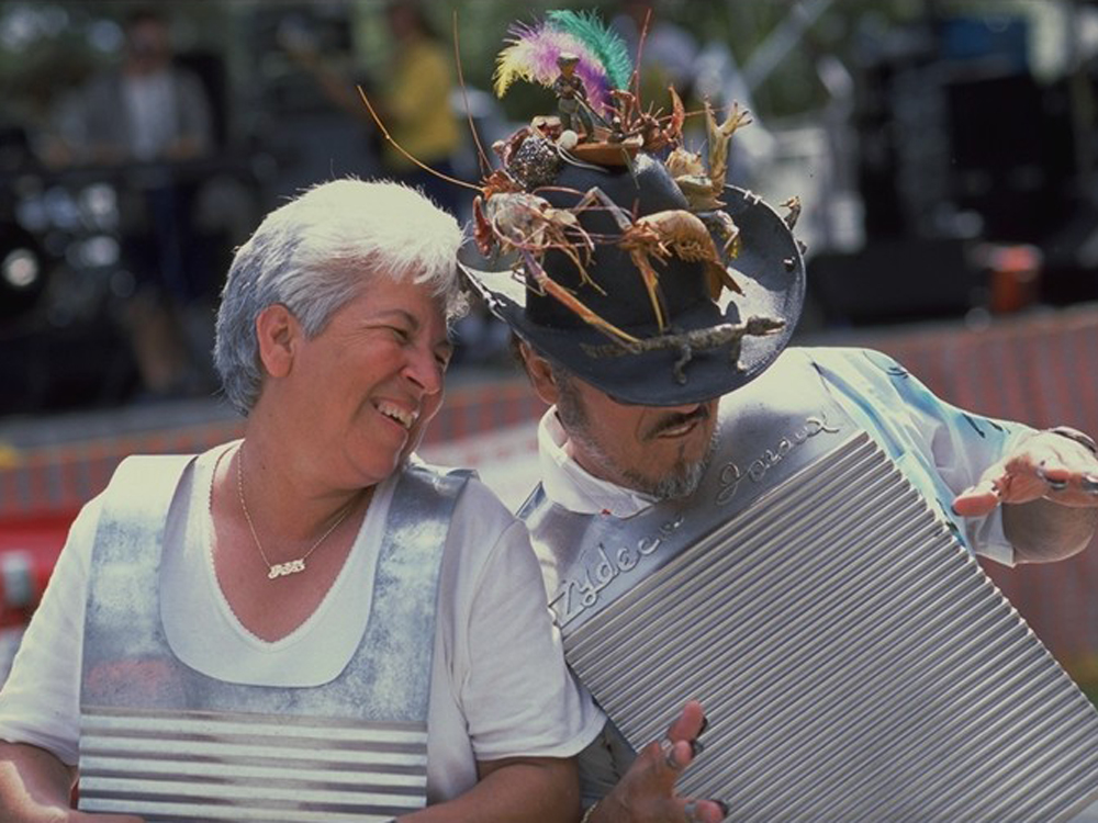 A man with a hat festooned with shrimp and a woman wear percussion washboards and smile.