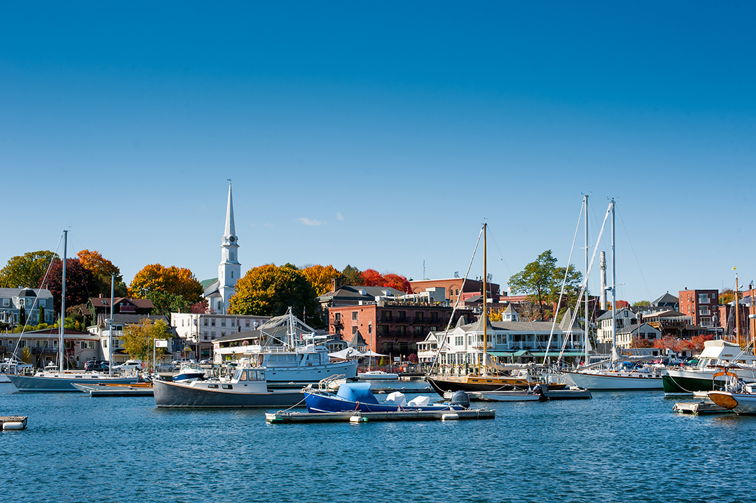 Several boats are moored in a harbor with an elegant white church steeple in the background.