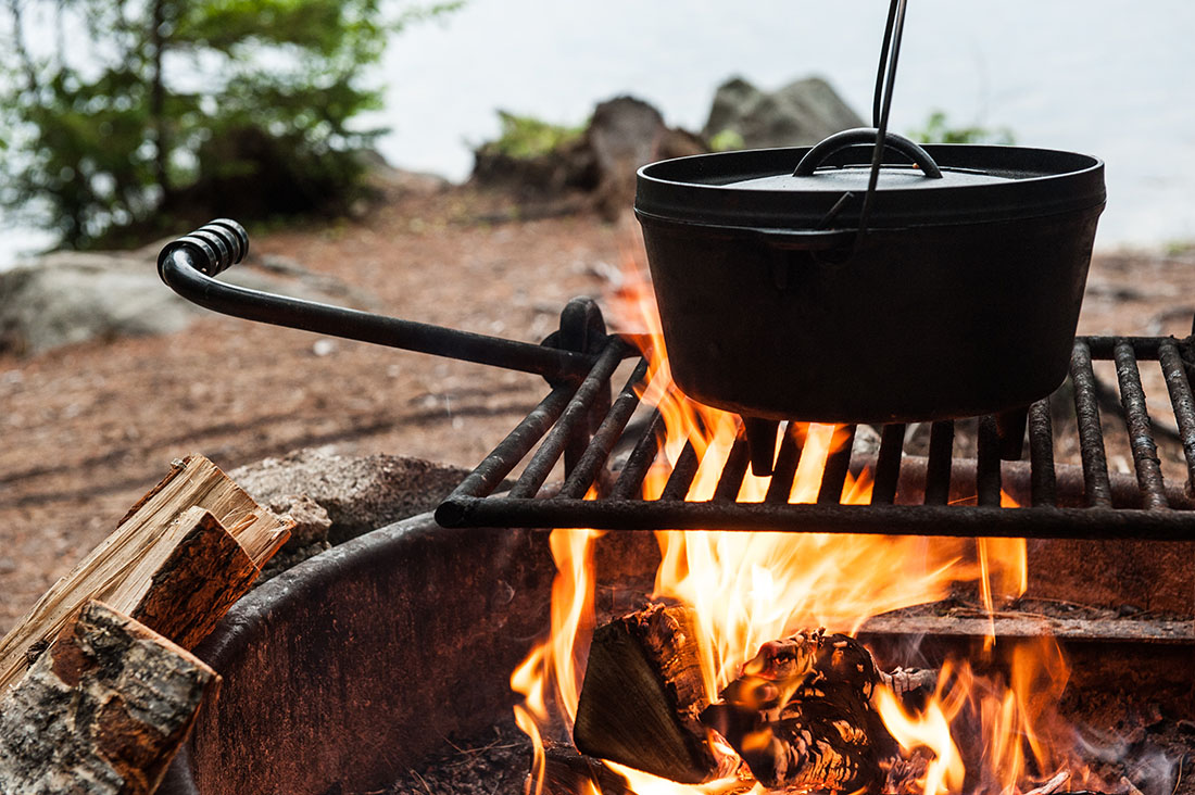 A dutch oven sits on a grill on a robust fire.