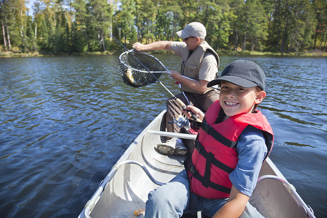 A father and son fish from a canoe.