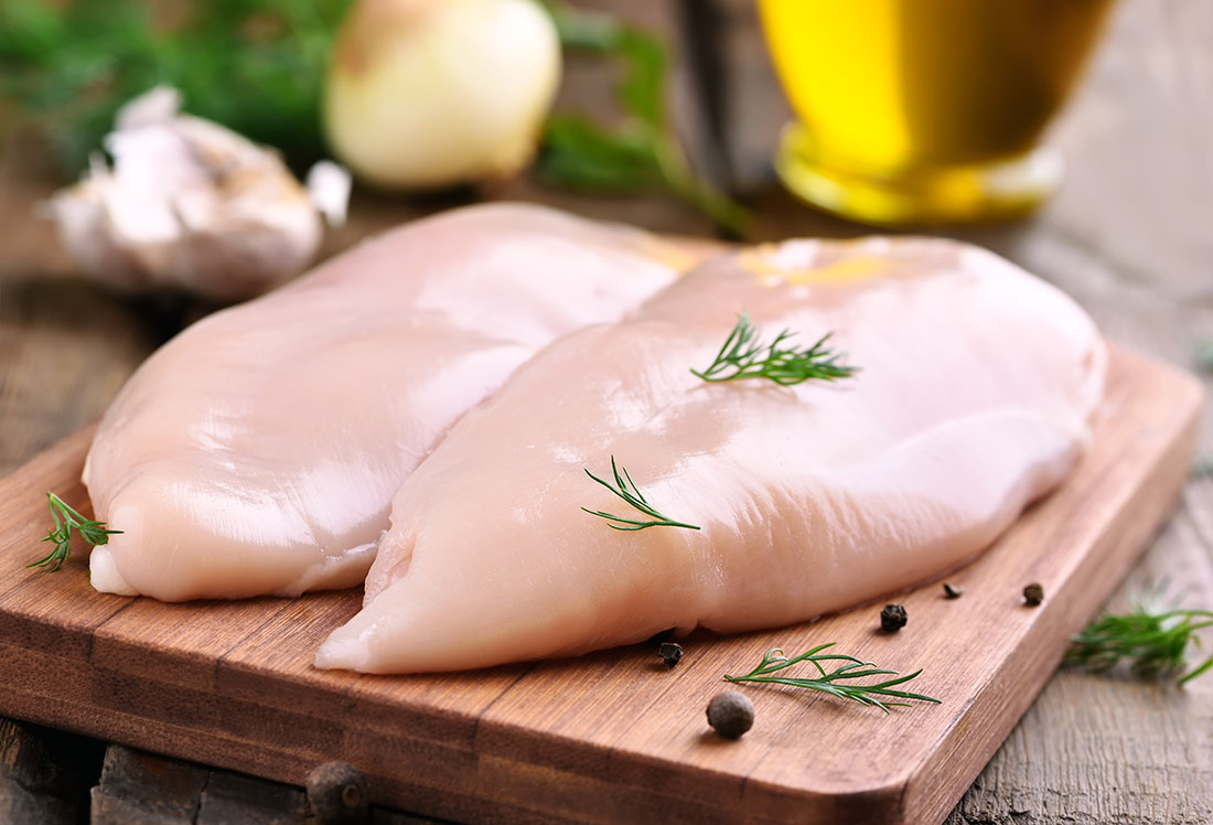 Two raw chicken breasts on a cutting board.