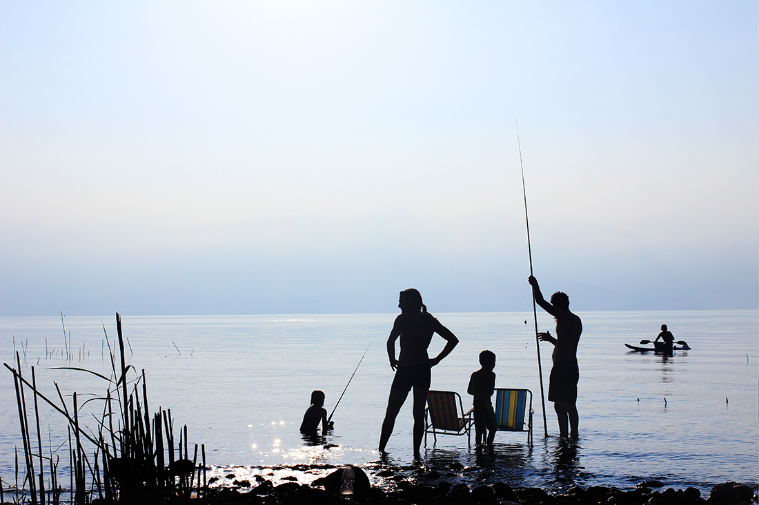 A family fishing silhouetted on a lake.