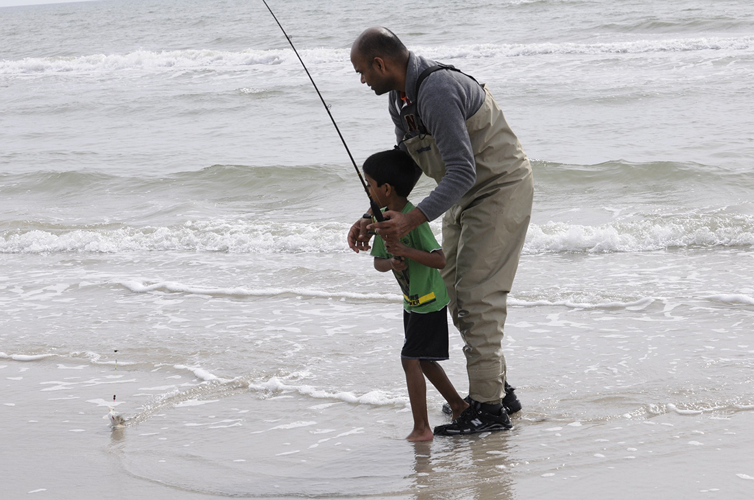 A father and son go ocean fishing.