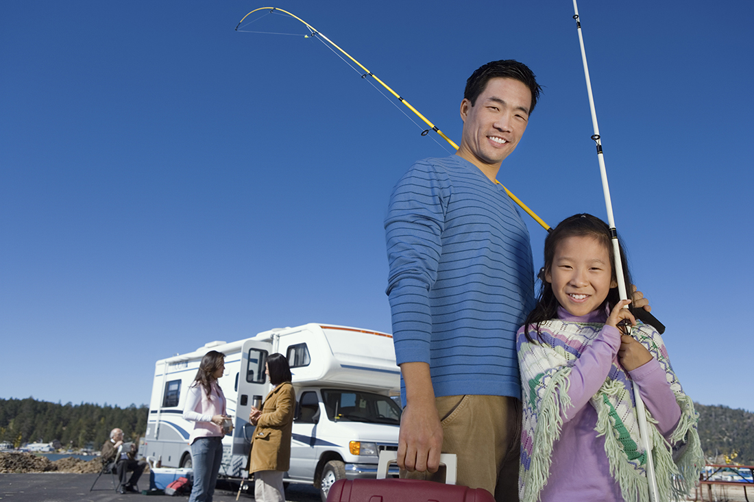 A father and daughter standing in front of an RV.