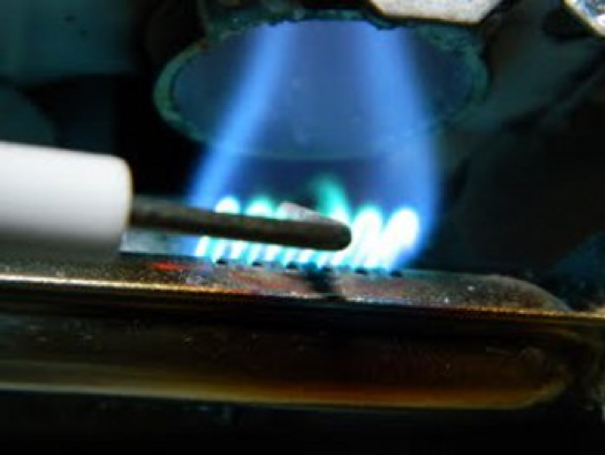 A fridge igniter electrode held against a flame.